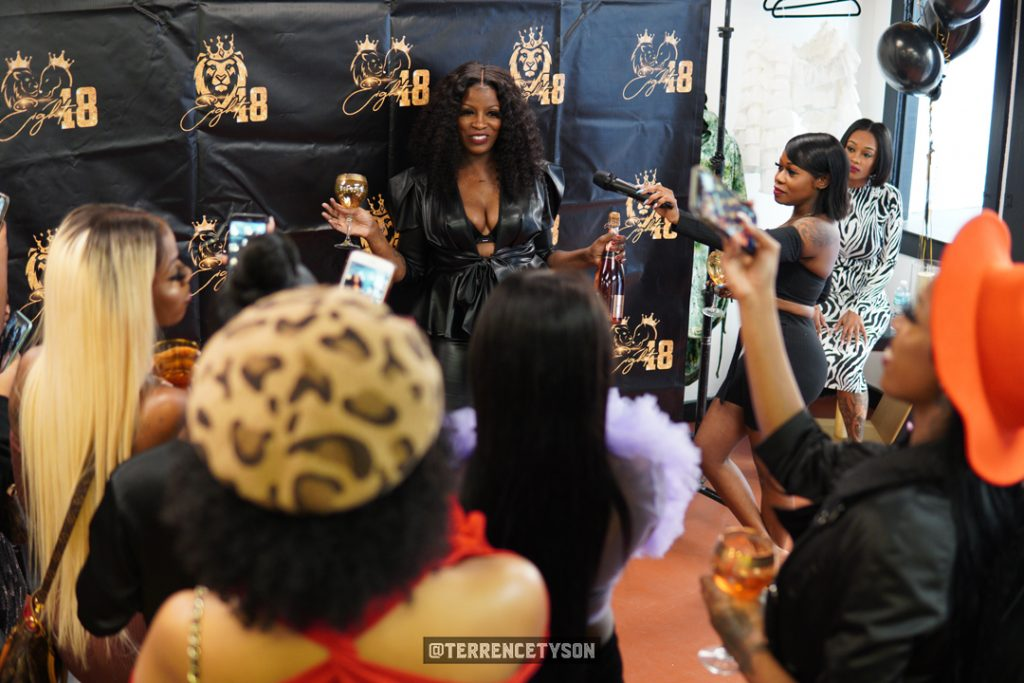 Carla Sheppard standing infant of crowd at Grand Opening of Eight18 Boutique