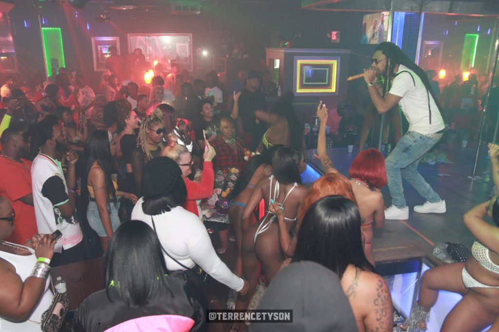 Rapper Iceberg standing on stage in front of crowd at nightclub