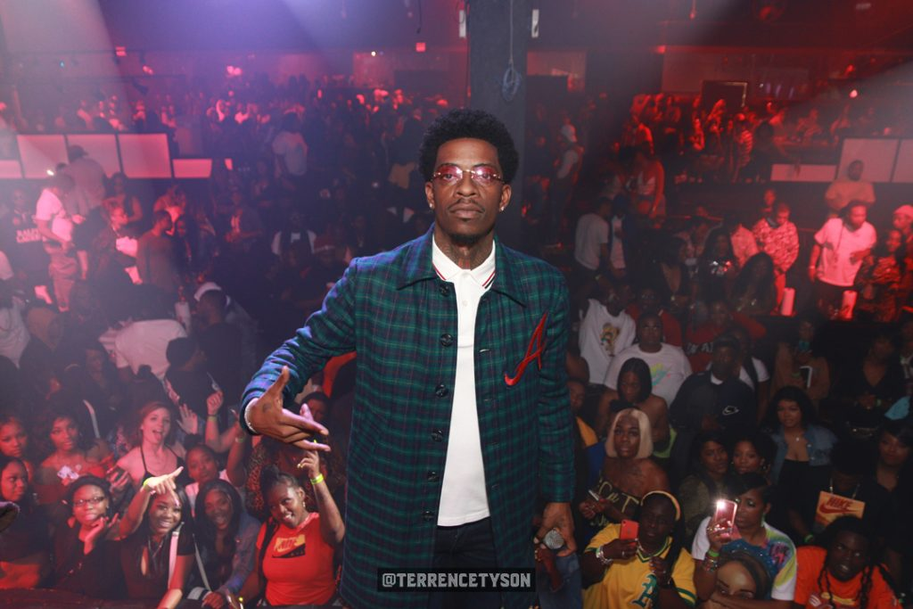 Rich Homie Quan standing on stage with audience crowd behind him